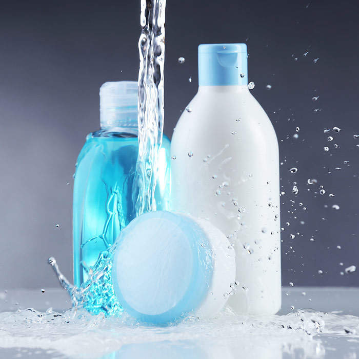 Blue And White Shampoo, Conditioner, And Moisturizer Bottles With Water Pouring On Them