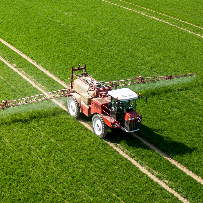 Farmer in tractor spraying crops