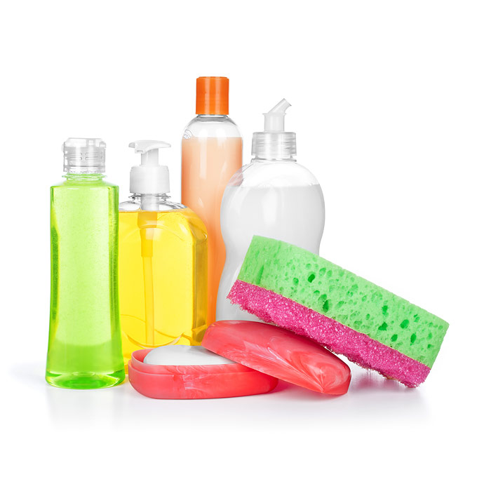Clear bottles of cleaning products, a sponge, and a bar of soap