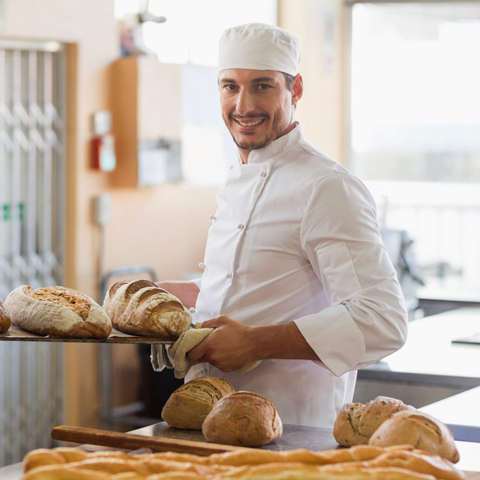 Smiling Man Baking Bread In A Restaurant