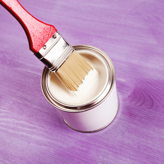 Paint brush being dipped in can of white paint